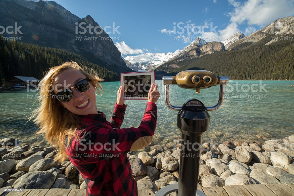 Woman photographing landscape using digital tablet-Lake Louise stock photo