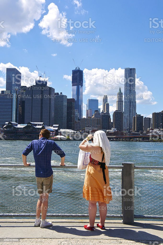 Woman photographing Manhattan skyline from Brooklyn park, NYC royalty-free stock photo