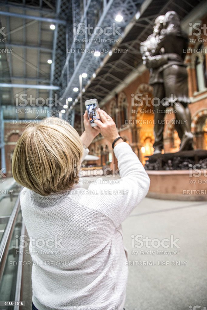Woman photographing statue at St. Pancras Station stock photo