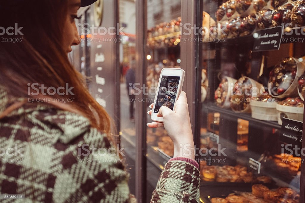 Woman photographing the candy shop window stock photo