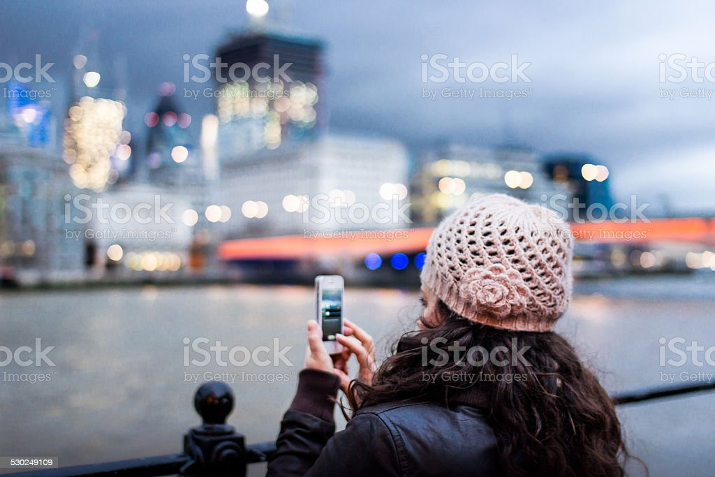 Woman photographing the London City skyline with smartphone stock photo