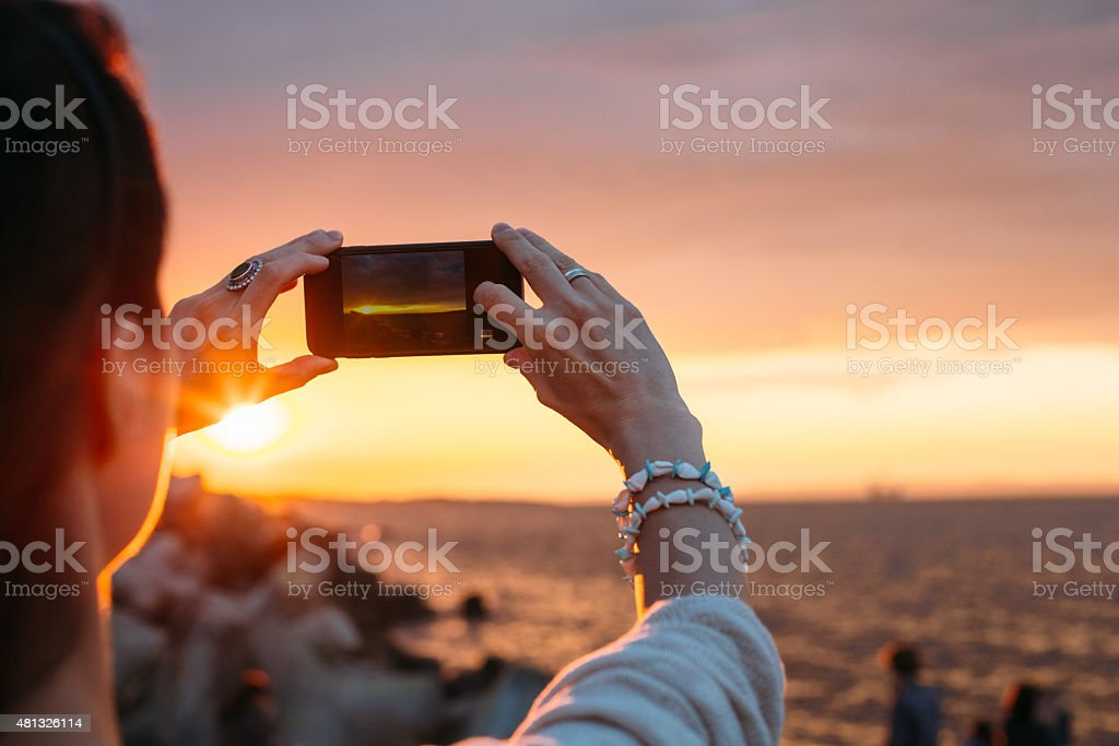 Woman photographing the sunset stock photo