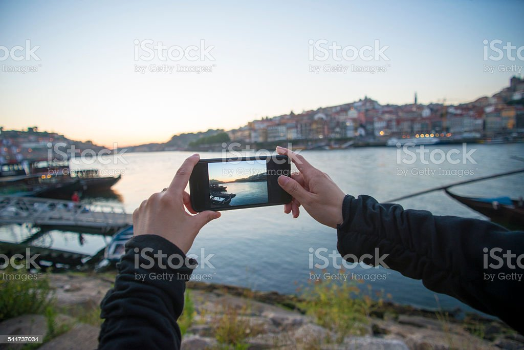 Woman photographing view at dusk stock photo