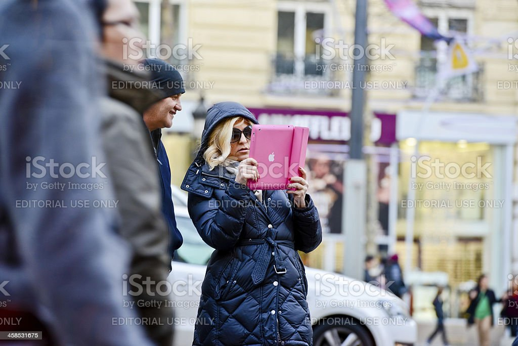 Woman photographing with iPad on Paris street royalty-free stock photo