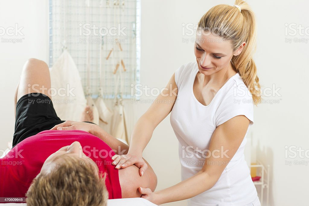 Woman physiotherapist helping patient with physical therapy royalty-free stock photo