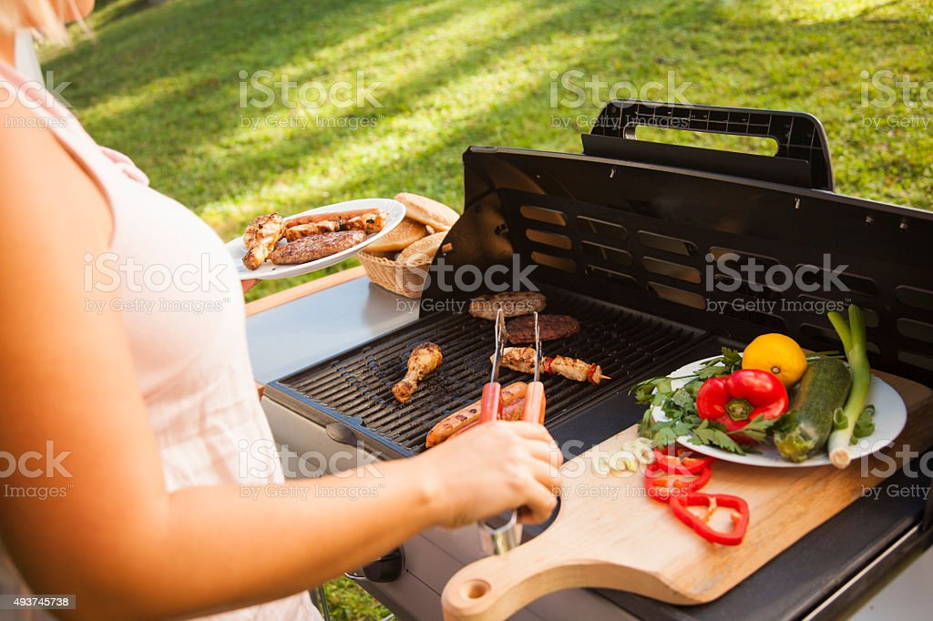 Woman picking meat from barbecue. stock photo