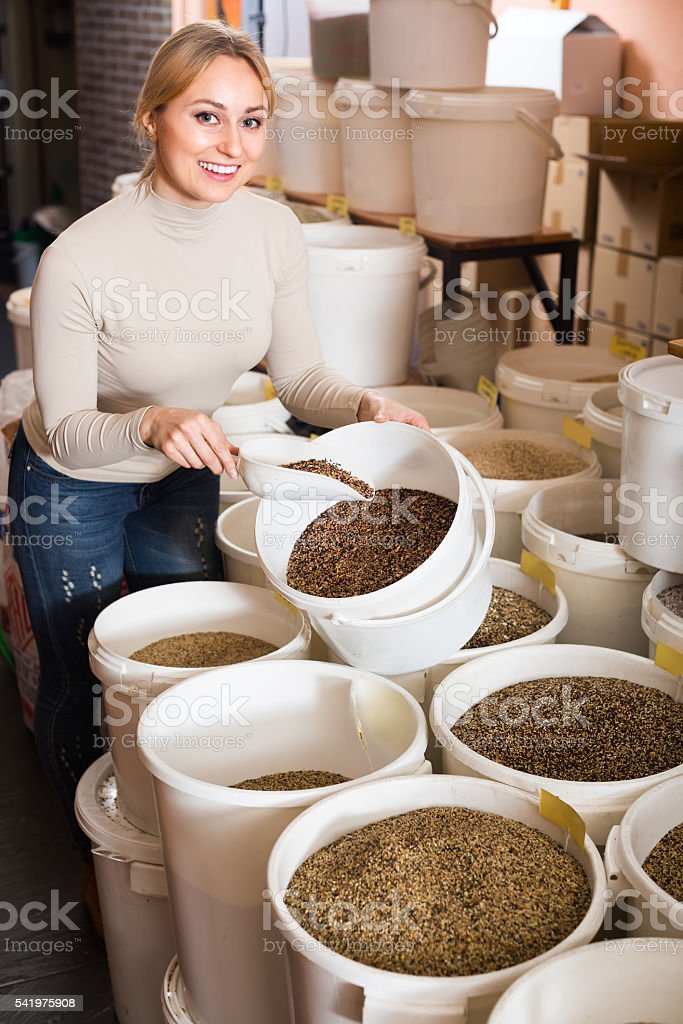Woman picking seeds for birds in shop stock photo