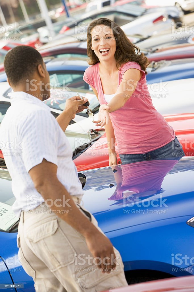 Woman picking up keys to new car royalty-free stock photo