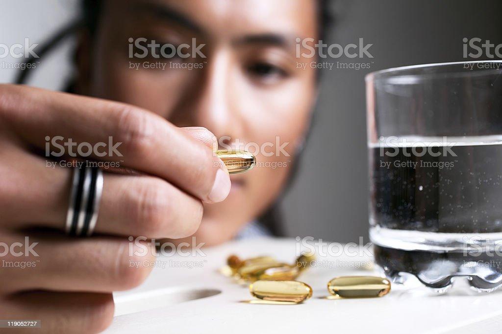 Woman picking up medicine to take royalty-free stock photo