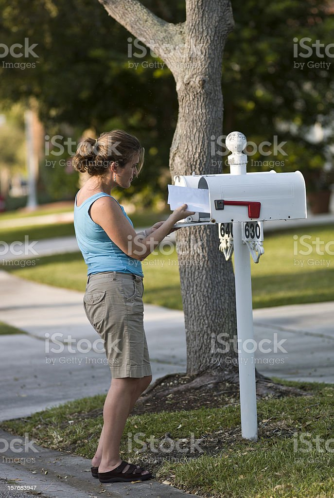 Woman picking up the mail stock photo