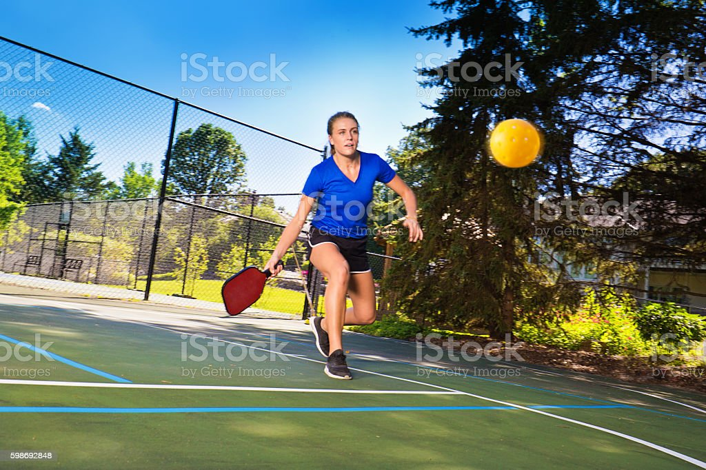 Woman Pickleball Player Playing Pickleball in Court stock photo