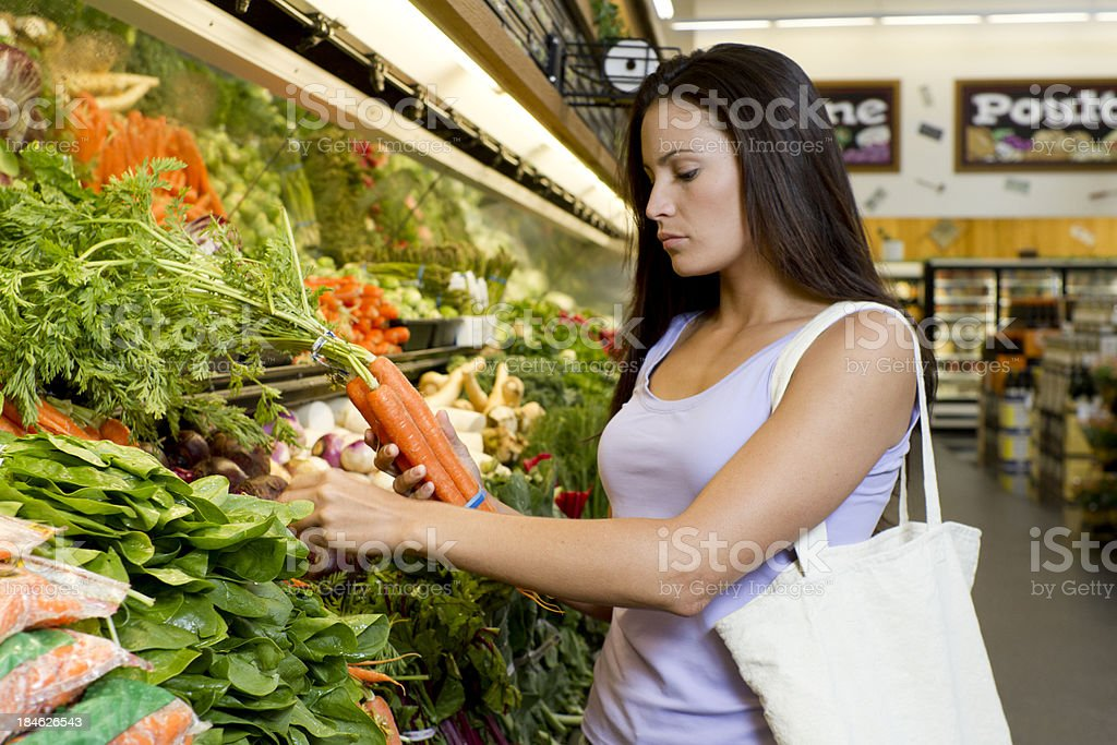 Woman Picks Out Carrots royalty-free stock photo