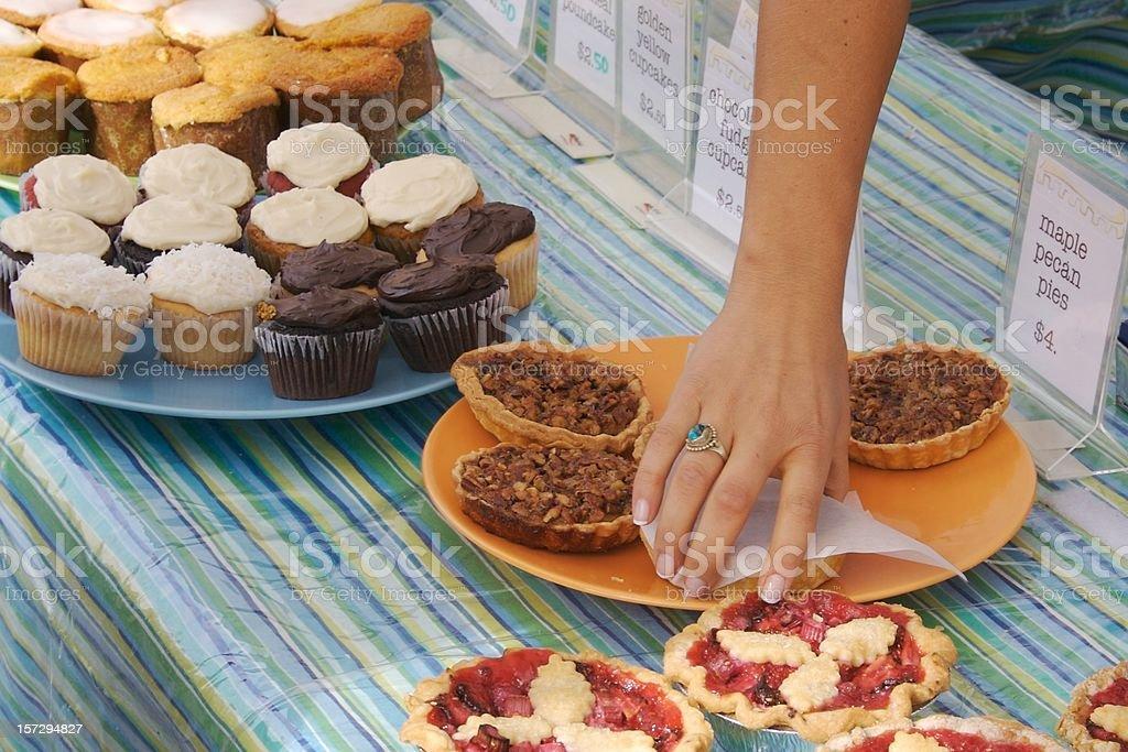 Woman picks up maple pecan pie, charity fundraiser bake sale stock photo