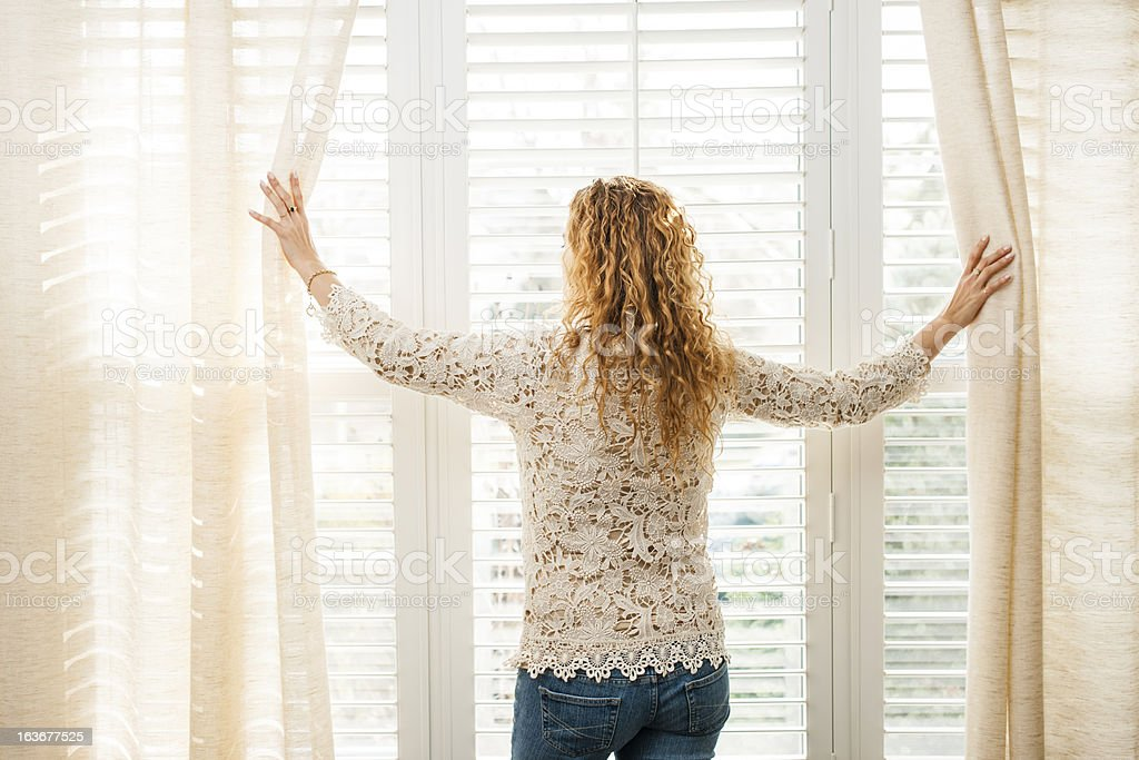 A woman pictured looking out of a window stock photo