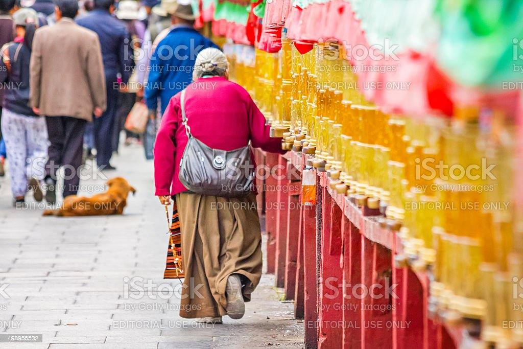 Woman Pilgrim Turns Prayer Wheels in Lhasa Tibet China stock photo
