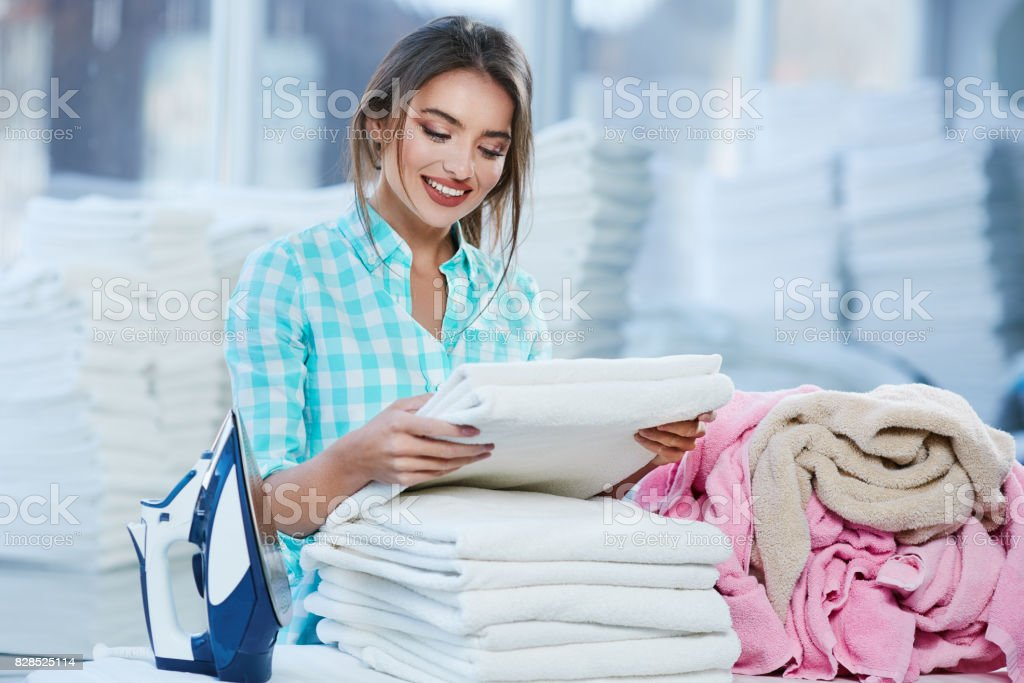 Woman piling white linen into heap stock photo