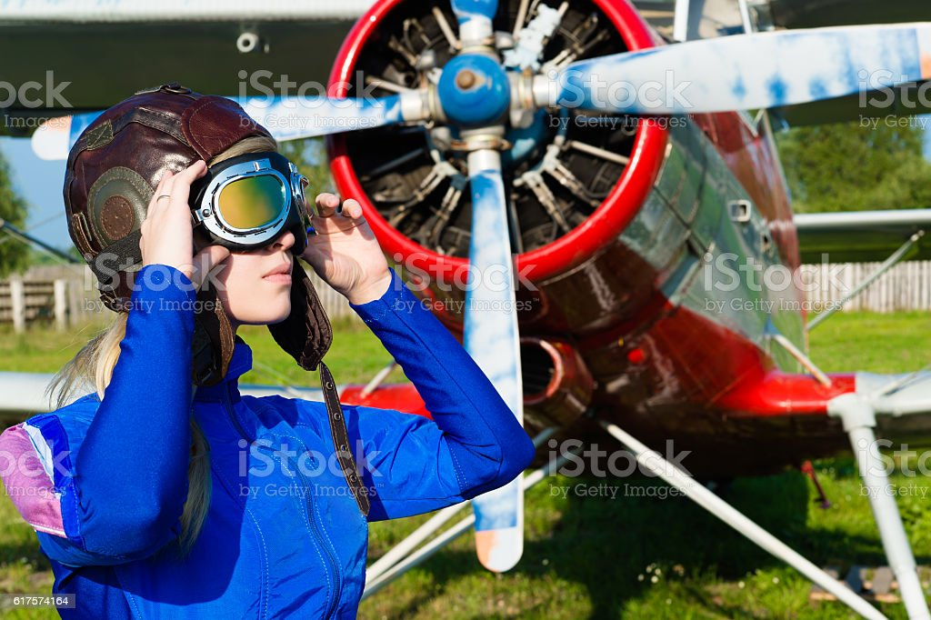 woman pilot in helmet on background of airplane stock photo