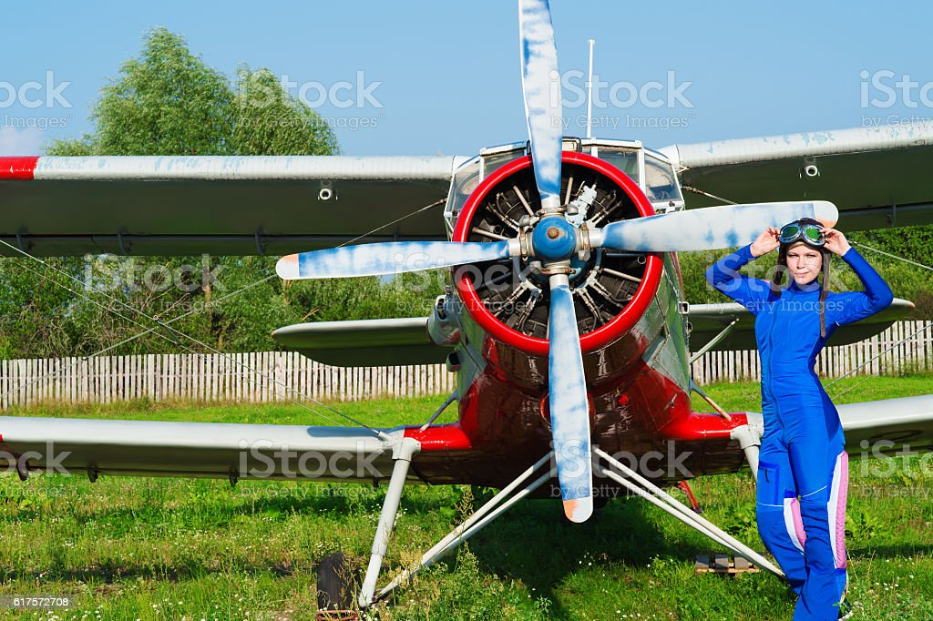 woman pilot in helmet standing with airplane stock photo
