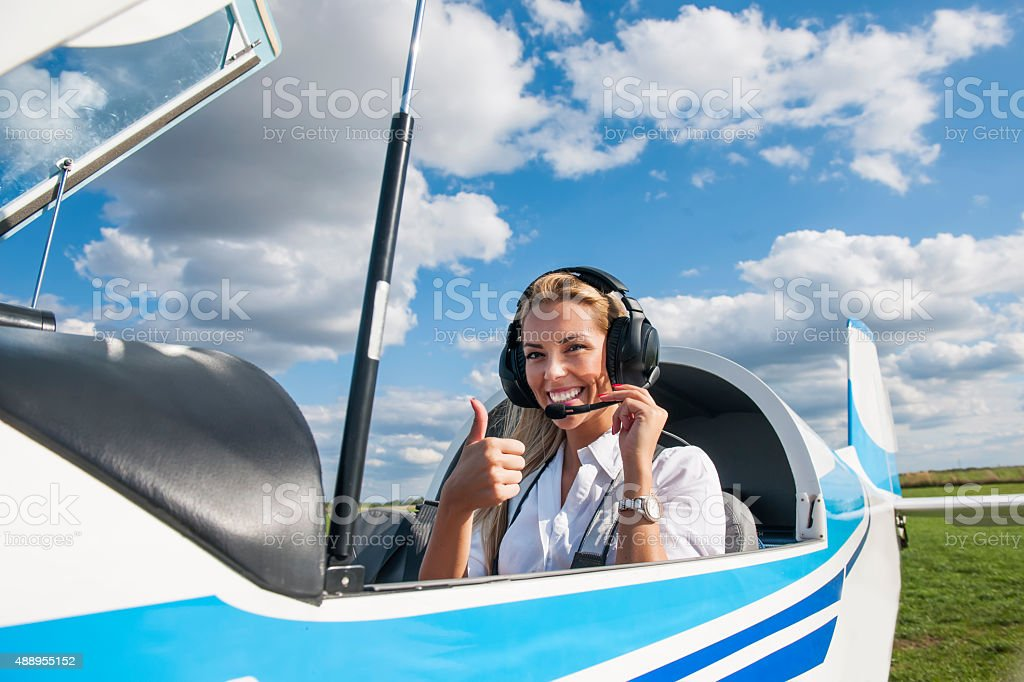 Woman pilot looking at camera, preparing for flying stock photo