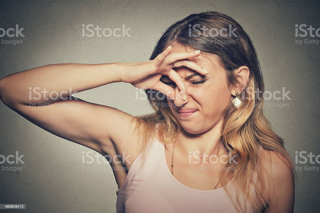 woman pinches nose looks with disgust stinks bad smell stock photo