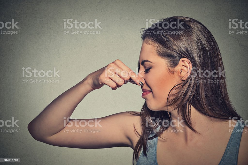 woman pinches nose with fingers looks with disgust stock photo