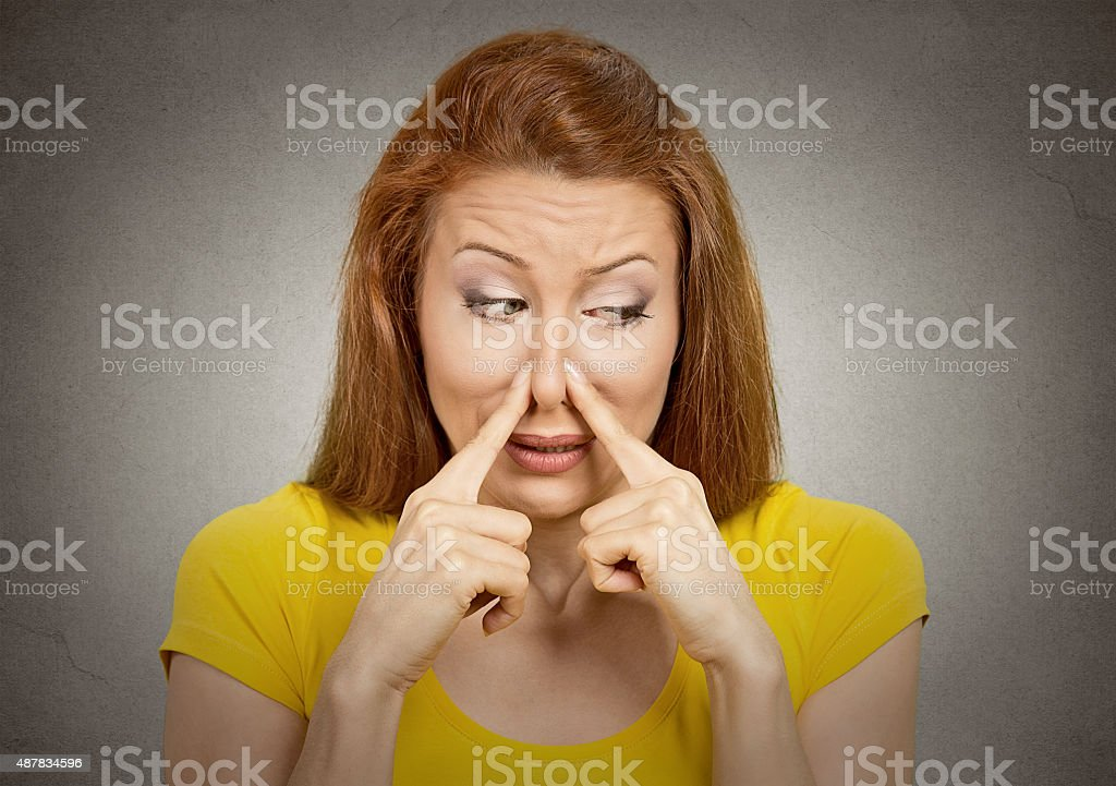woman pinches nose with fingers something stinks stock photo