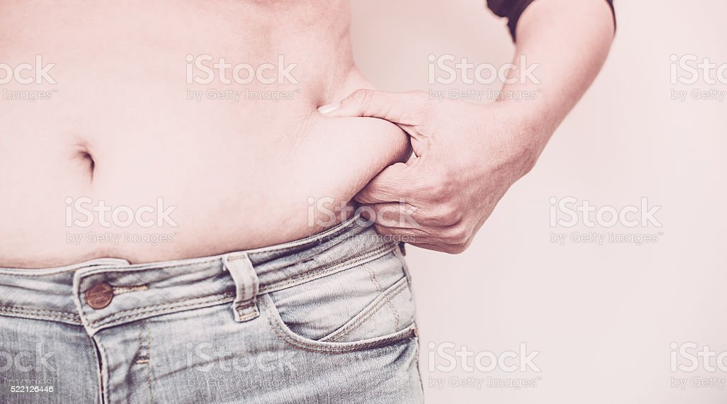Woman Pinching Fat on her waist stock photo