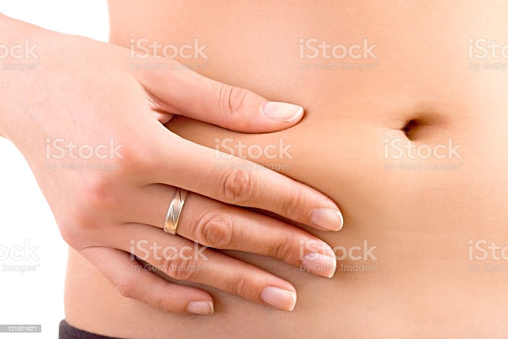 A woman pinching her stomach fat with a close-up view royalty-free stock photo