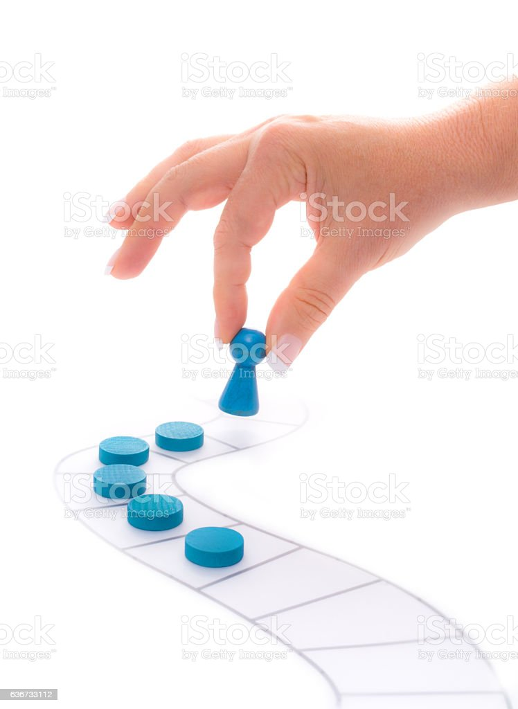 Woman places blue pawn on a path stock photo