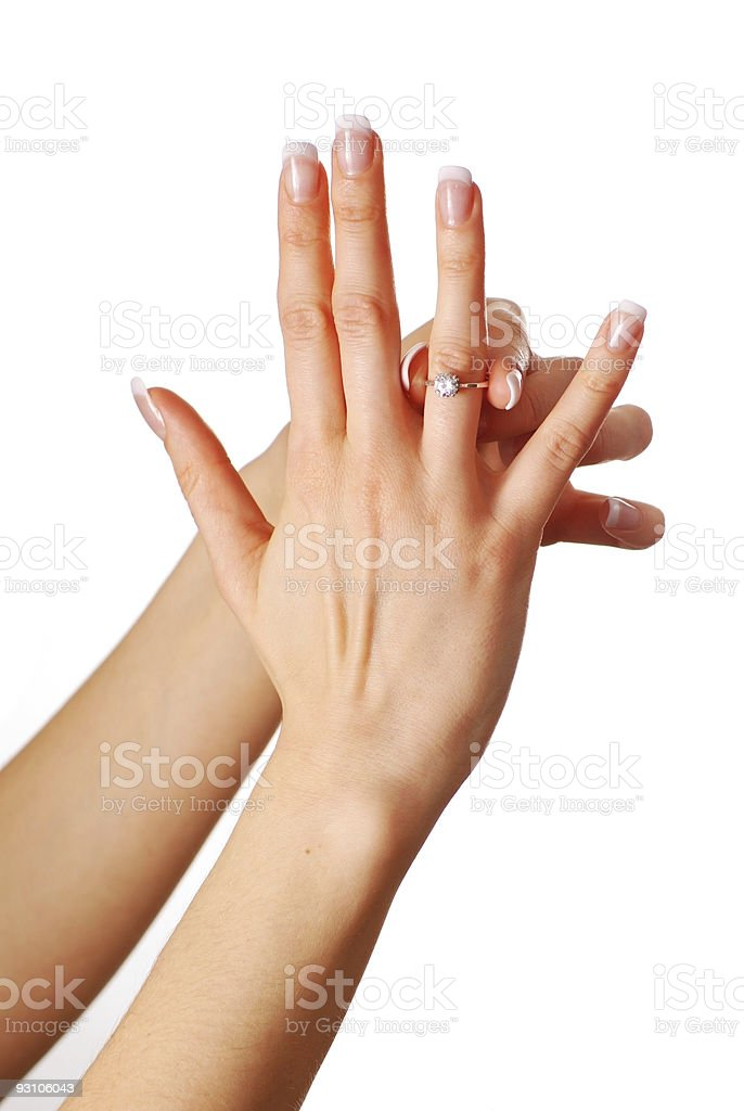 Woman placing a diamond ring on her finger stock photo