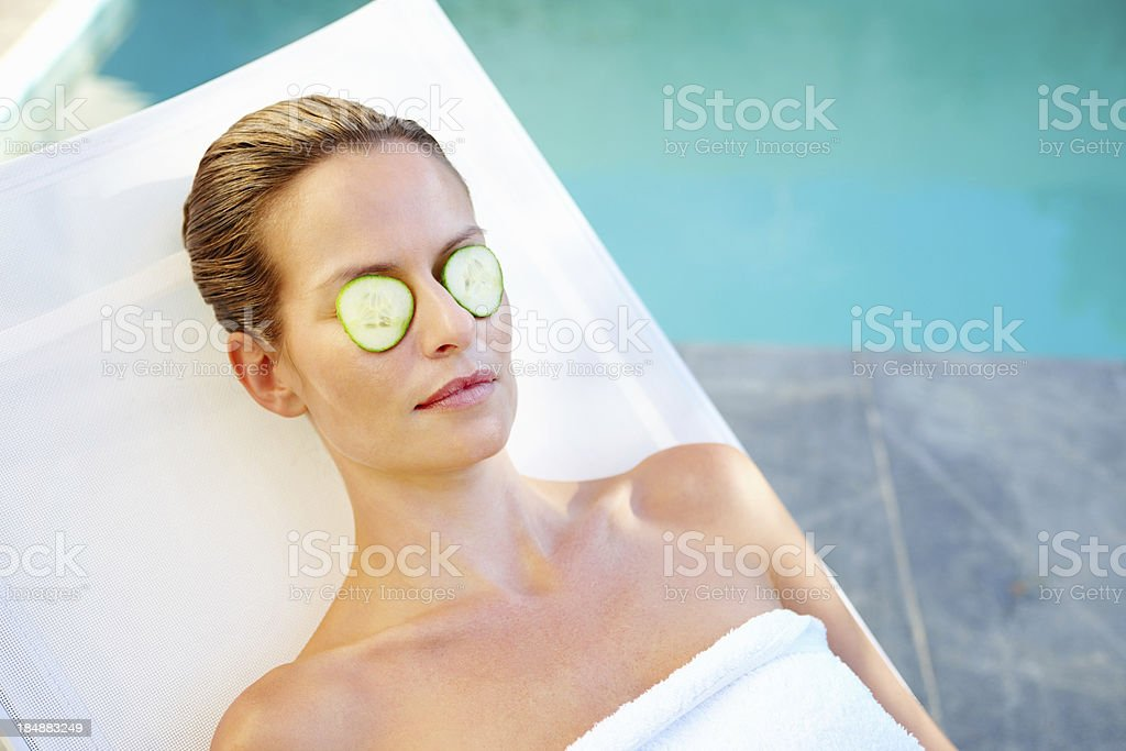 Woman placing cucumber slices royalty-free stock photo