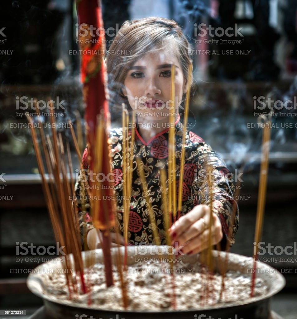 Woman Placing Incense Sticks In A Vietnamese Temple stock photo