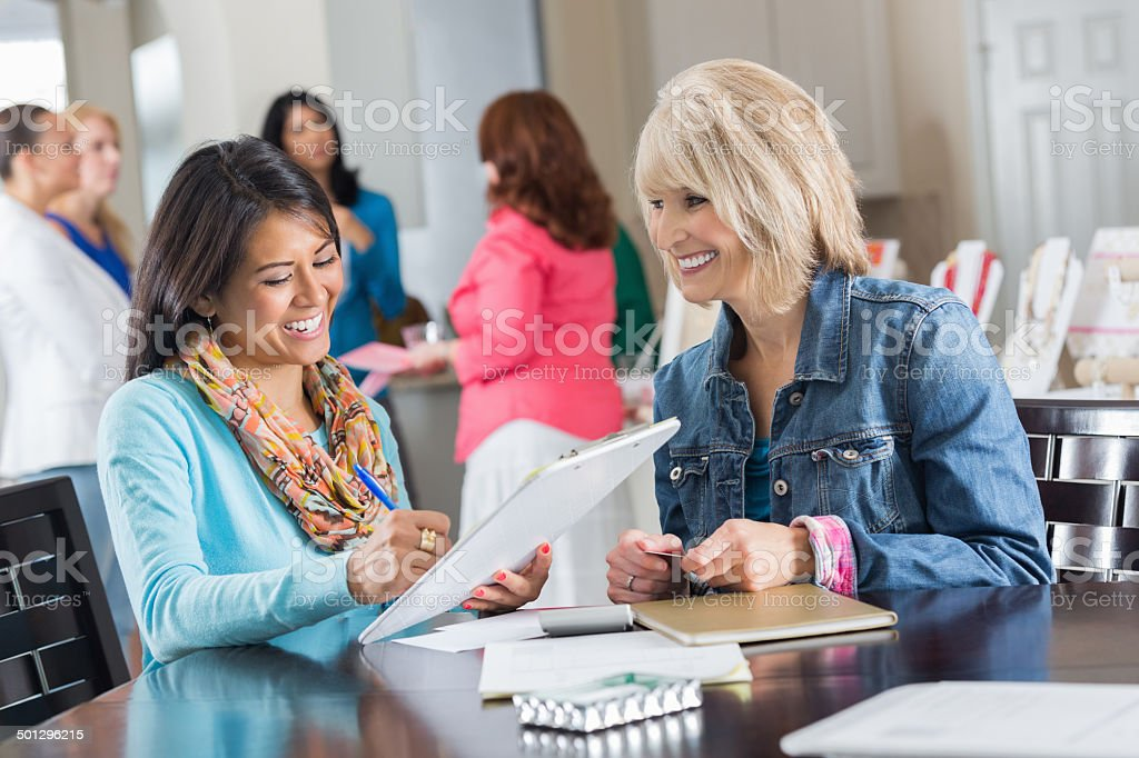Woman placing order for jewelry at home sales party stock photo