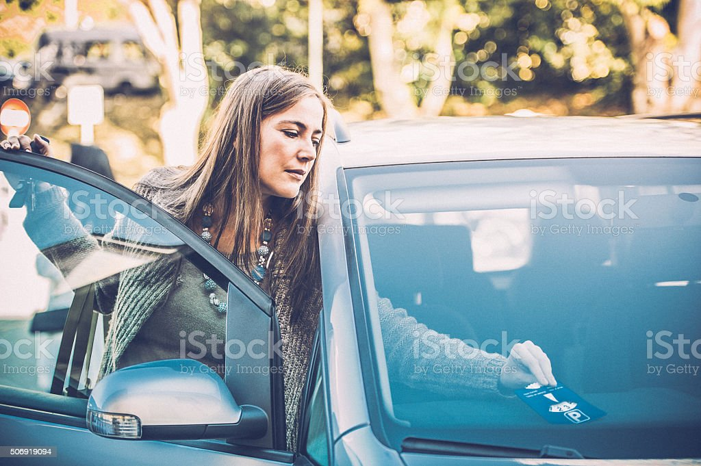 Woman Placing Parking Clock on Car Dashboard stock photo