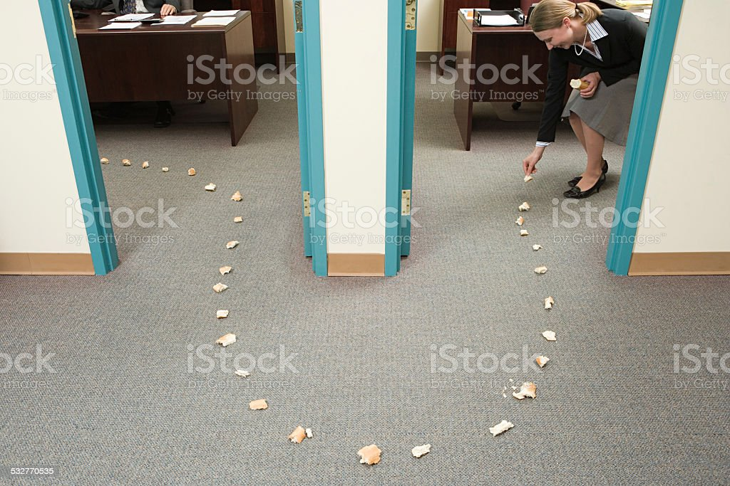 Woman placing trail of bread stock photo