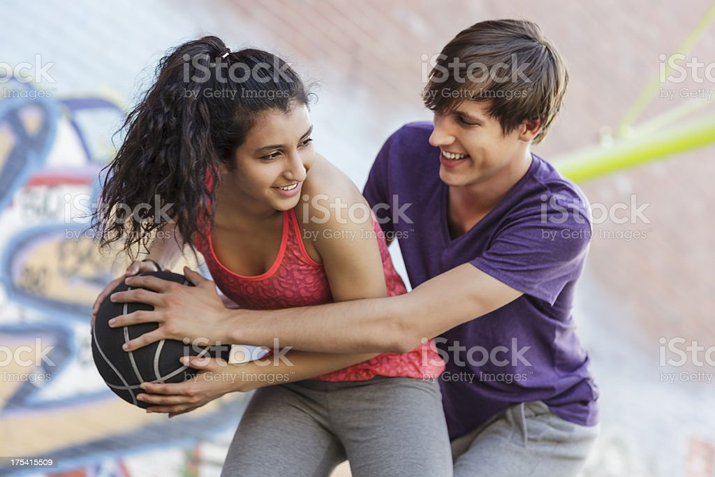 Woman Playing a Game of Basketball Against Man stock photo