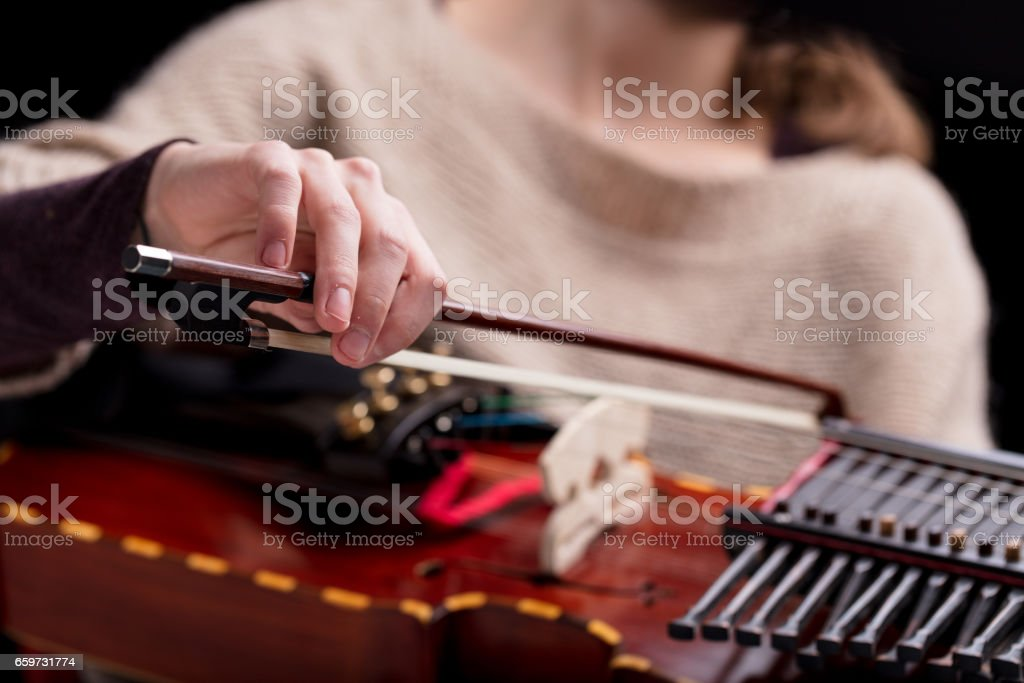 woman playing a nyckelharpa musical instrument stock photo