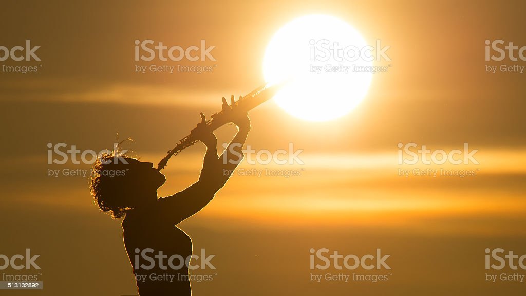 Woman playing a saxophone at the sun stock photo