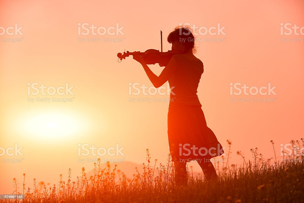 Woman playing a violin in a red sunset in nature stock photo