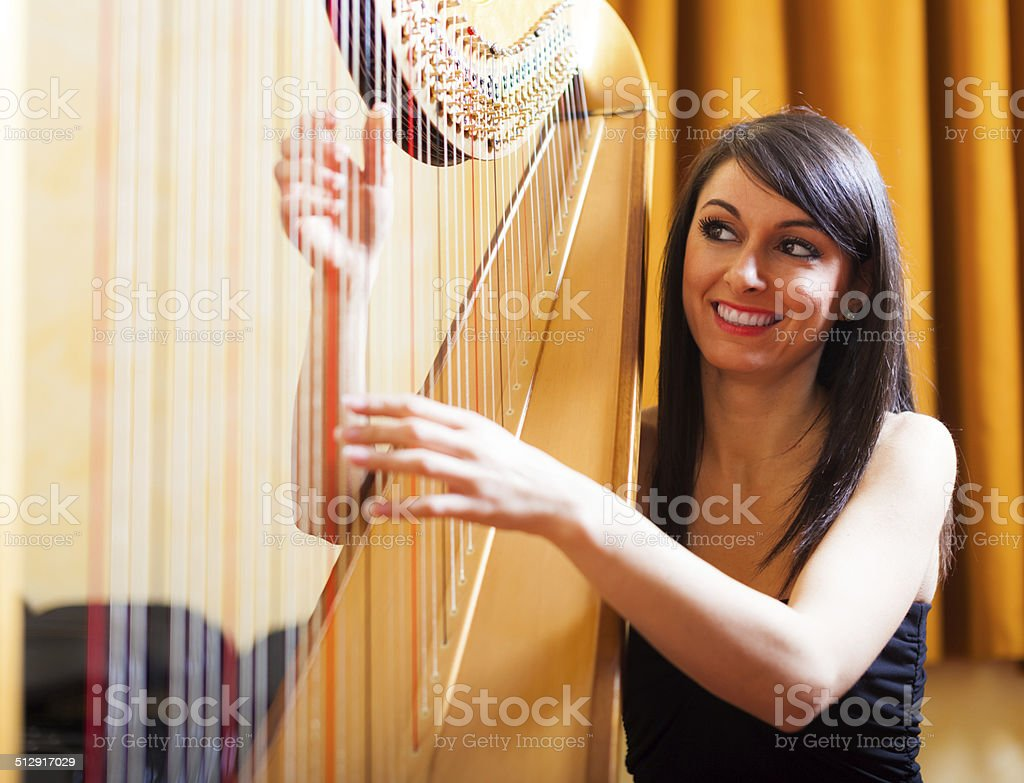 Woman playing an harp stock photo