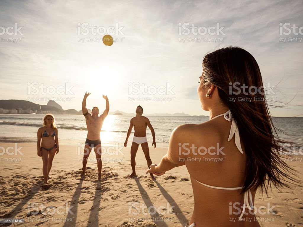 Woman playing beach volleyball with her friends during summer day. stock photo