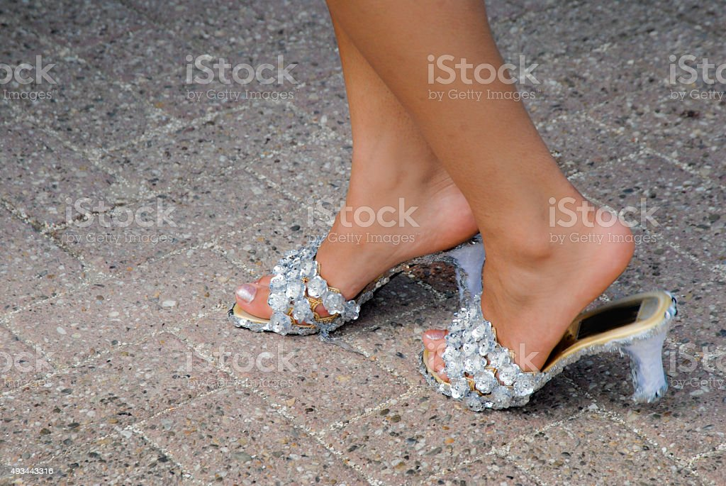 Woman playing cinderella with rhinestone decorated mules stock photo