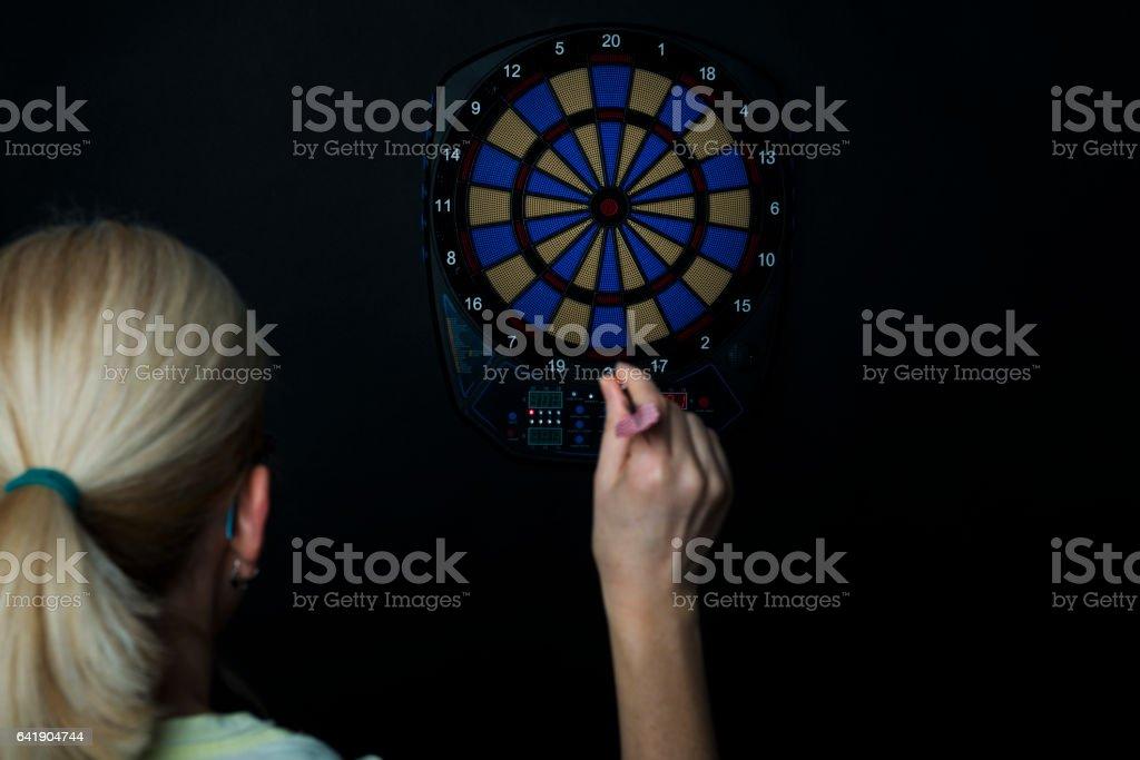 woman playing dart on electronic dartboard stock photo