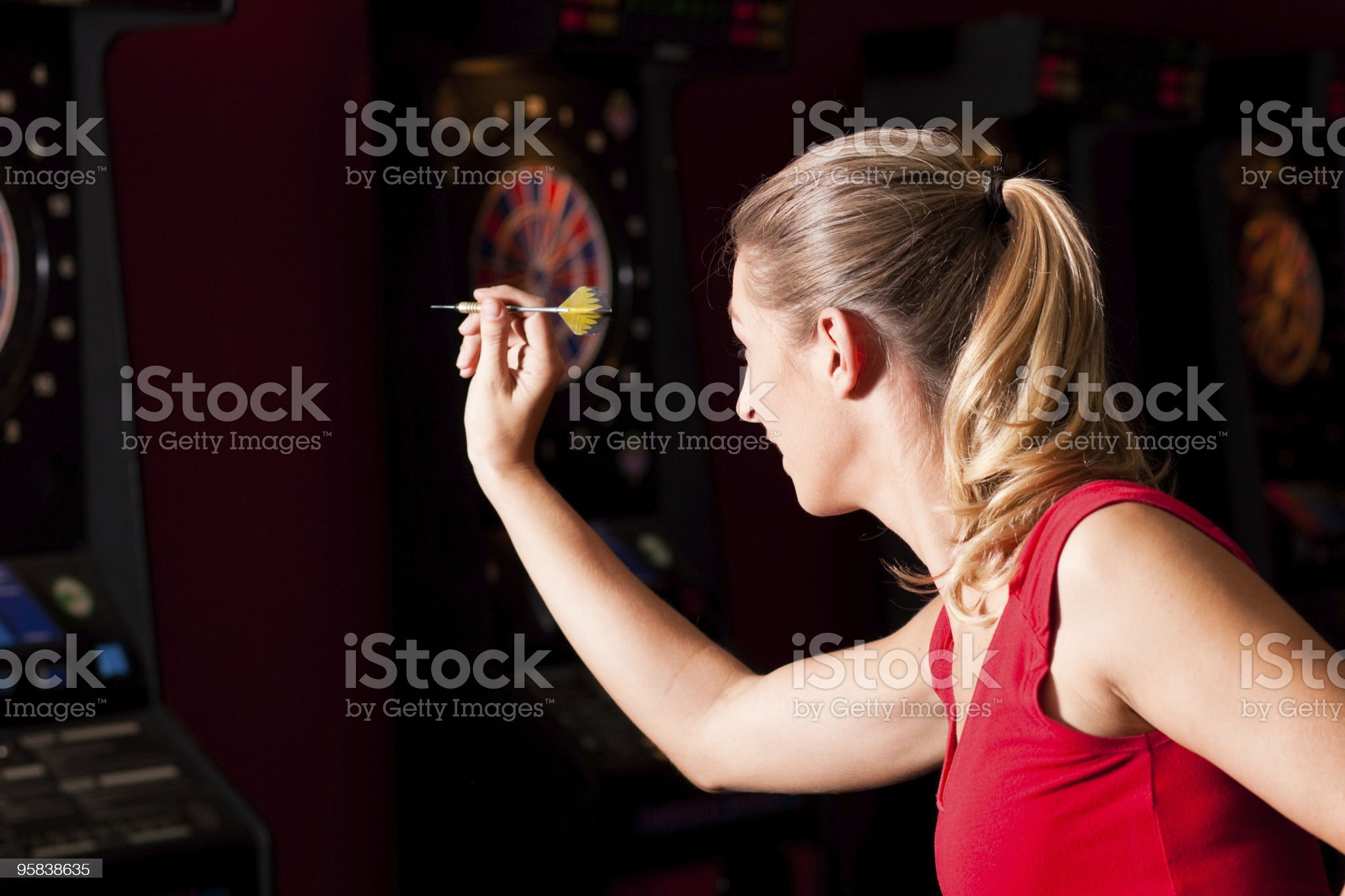 Woman playing darts in a red dress royalty-free stock photo
