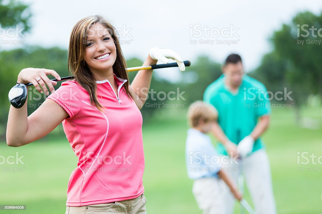 Woman playing golf with family stock photo