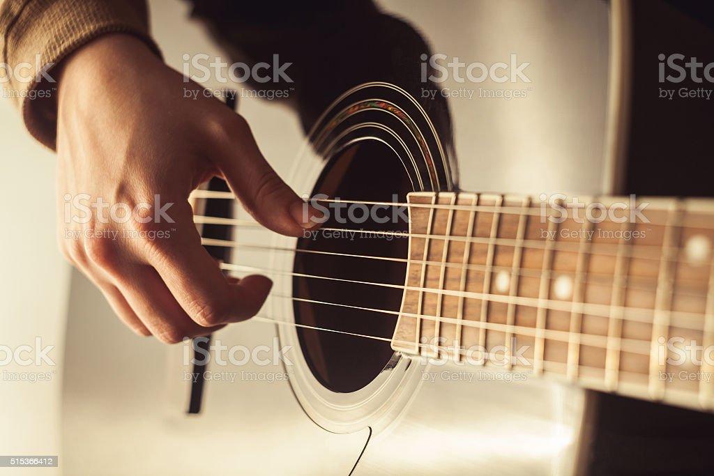 Woman playing guitar close-up shot stock photo