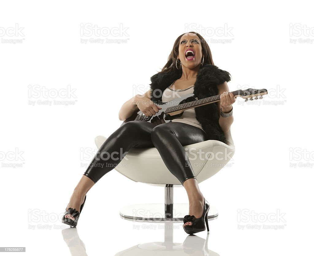 Woman playing guitar on a chair royalty-free stock photo