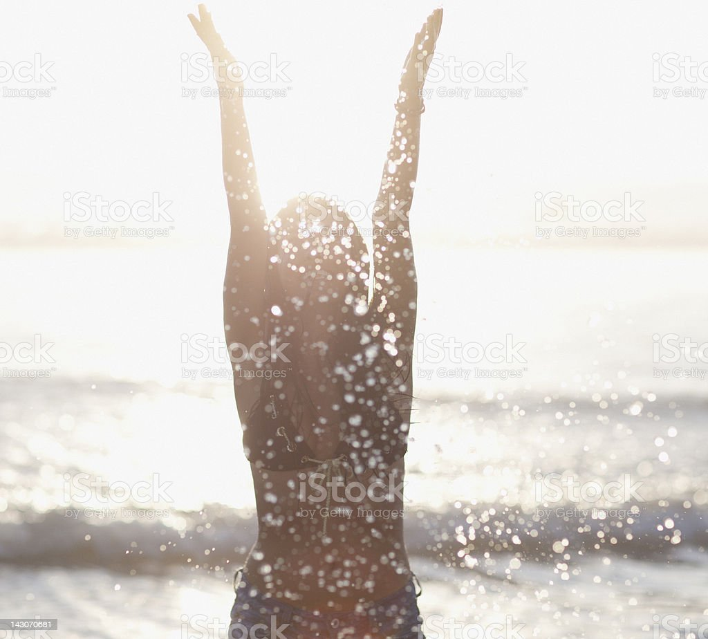 Woman playing in waves at beach royalty-free stock photo