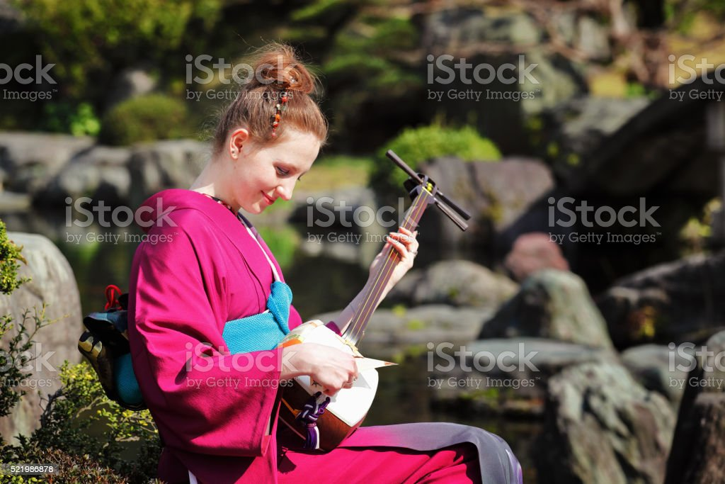 Woman playing Japanese traditional guitar in garden stock photo