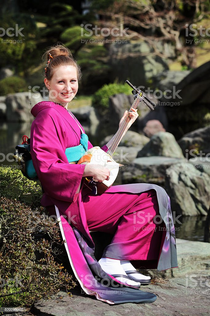 Woman playing Japanese traditional guitar stock photo